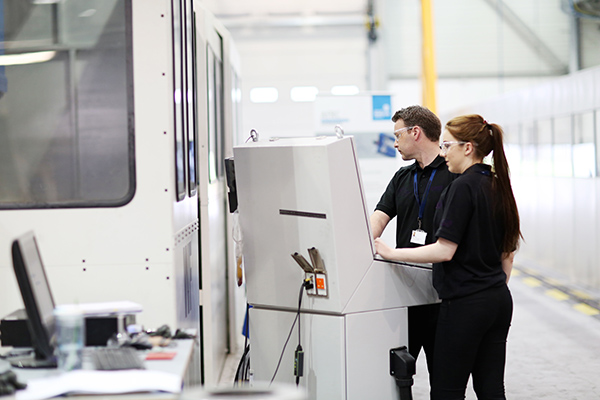 Young engineers operate a machine tool
